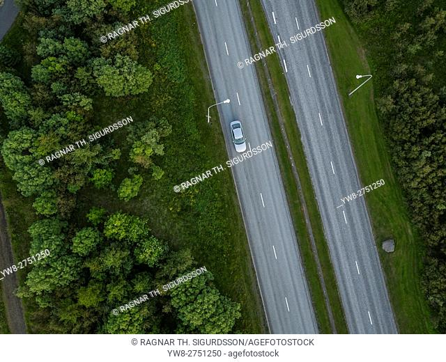 Top view of single car driving alone on the road, Reykjavik, Iceland. This image is shot using a drone