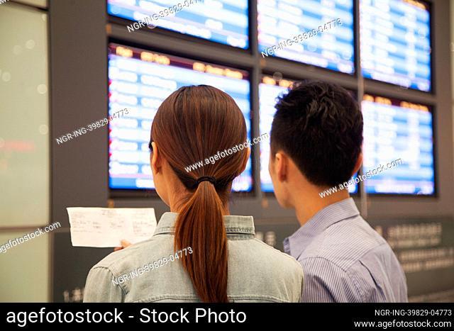 Two travelers looking at flight departure screens at airport