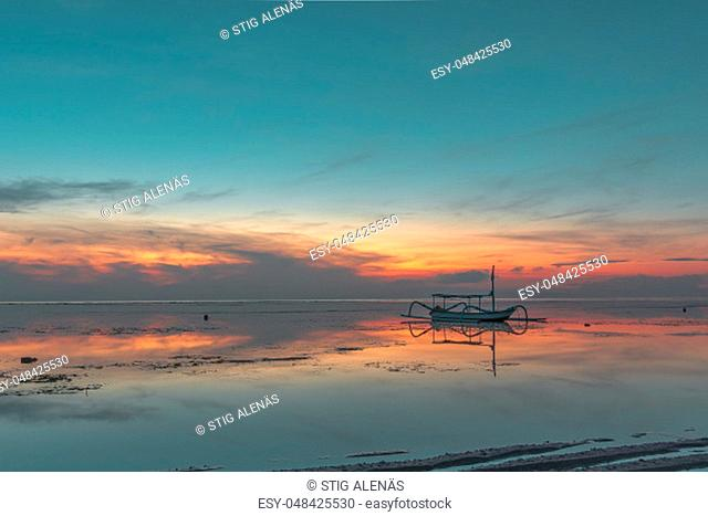 Indonesian fishing boat at twilight time, close to the shore, red reflections in the water, Sanur, Bali, Indonesia, April 21, 2018