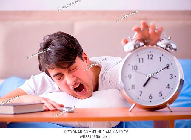 Man in bed frustrated suffering from insomnia with an alarm clock