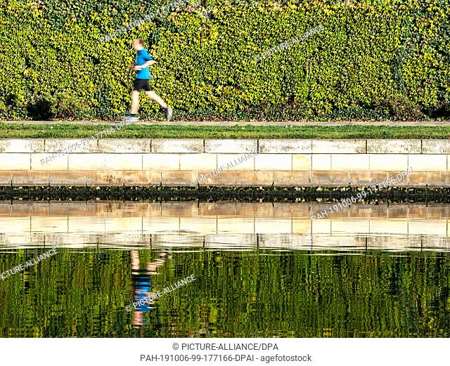 06 October 2019, Berlin: A man jogging on the Spree in the morning in the government district. (long exposure) Photo: Paul Zinken/dpa