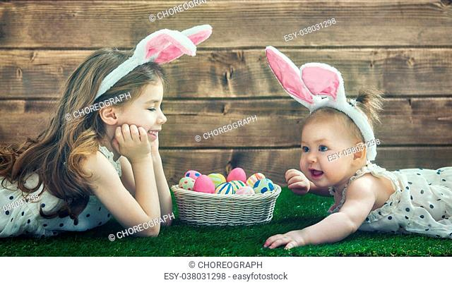 Happy Easter! Cute little children girls wearing bunny ears on Easter day. Sisters hunting for Easter eggs on the lawn near the house