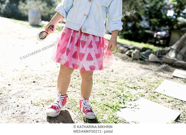 Little girl wearing fashionable skirt, partial view