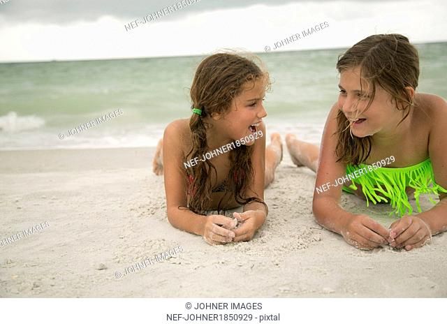 Two girl lying on beach
