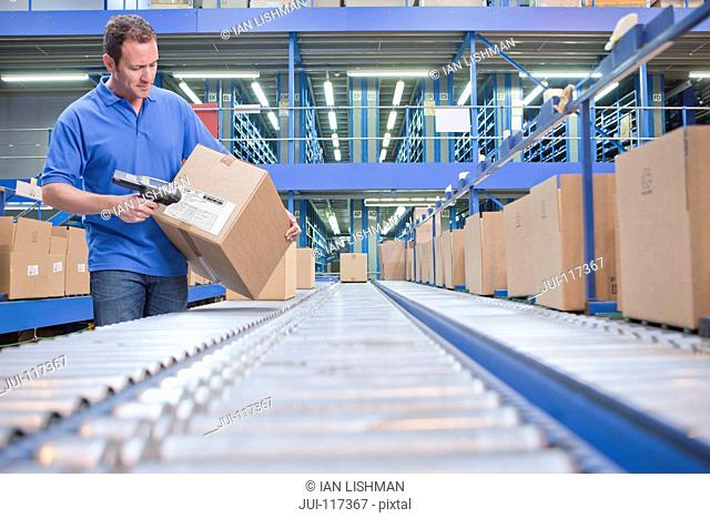 Worker Using Scanner In Warehouse Despatch Area