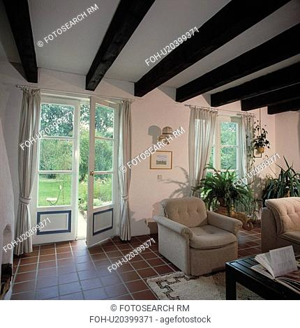 Tiled floor in white living room with French doors and beamed ceiling
