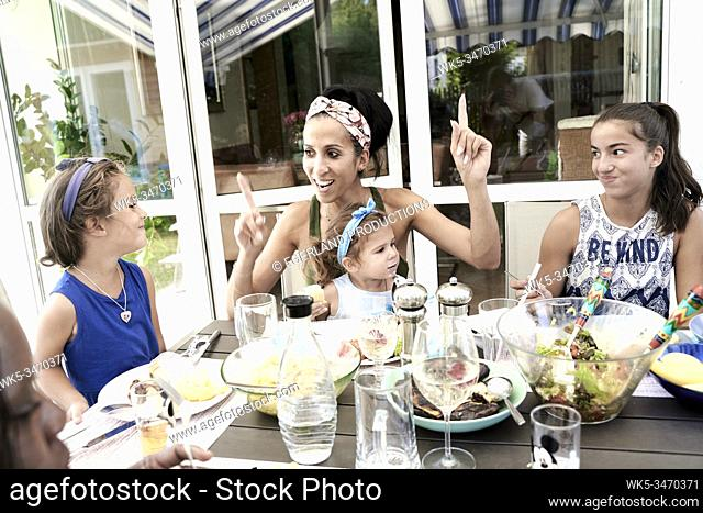Optimistic mother eating with children, pointing up fingers