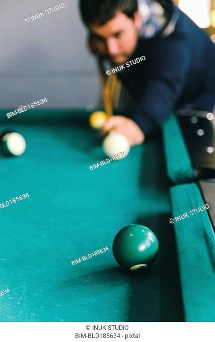 Hispanic man playing pool