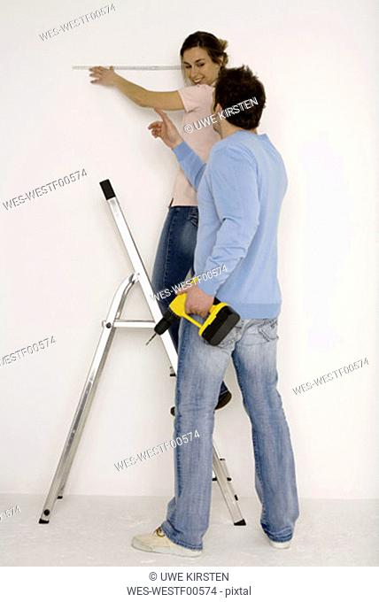Young couple, man holding electric drill, woman measuring wall with scale