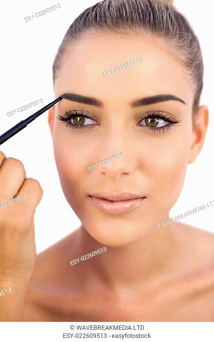 Smiling woman applying make up on her eyebrows