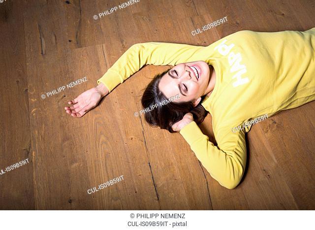 Happy young woman in yellow sweatshirt lying on wooden floor