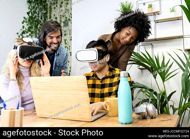 Businessman and businesswoman wearing virtual reality simulator by male and female colleague in office