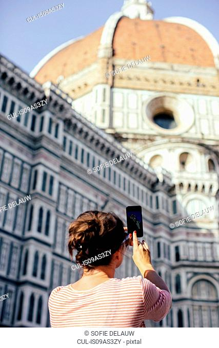 Low angle rear view of mid adult woman using smart phone to take photograph, Duomo Cathedral, Florence, Italy