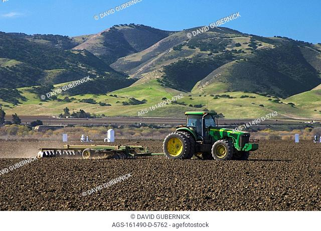 Agriculture - A John Deere tractor and field implement disk a recently harvested field in preparation for planting the next crop / CA - Salinas Valley