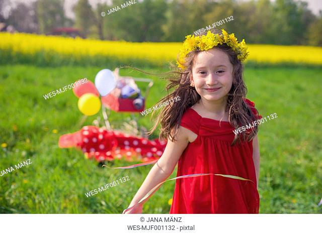 Portrait of smiling little girl wearing flowers and red summer dress