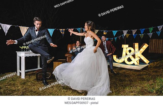 Happy bride and man dancing on a night field party