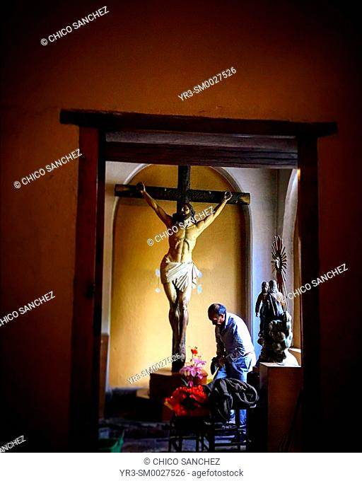 A man cleans a chapel decorated with an image of Jesus Christ crucified in San Angel, Mexico City, Mexico
