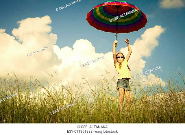 Girl jumping on the road with an umbrella in his hand
