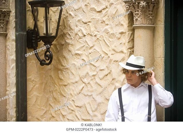 Young man in hat and suspenders outside next to building