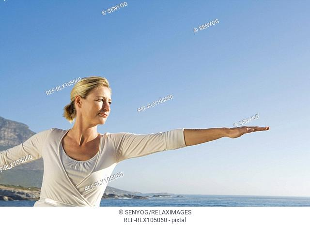 Mature woman with arms outstretched, side profile with ocean in background