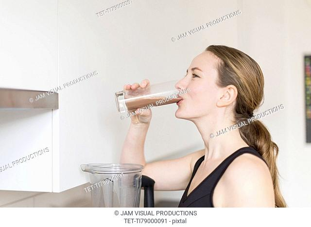 Mid-adult woman drinking smoothie