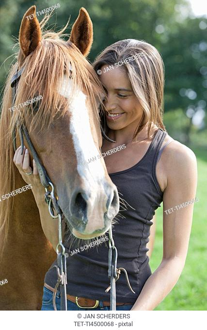Portrait of young woman with horse in field