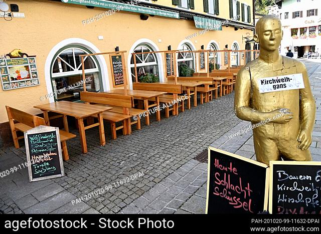 20 October 2020, Bavaria, Berchtesgaden: Empty tables and benches stand in front of a restaurant in the centre of the village