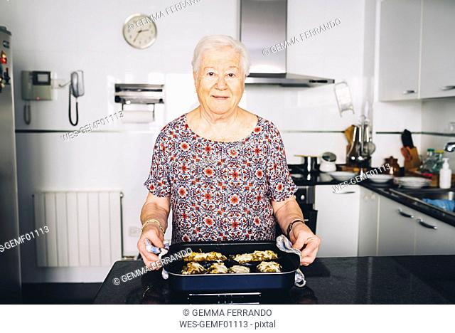 Portrait of senior woman with prepared food in the kitchen