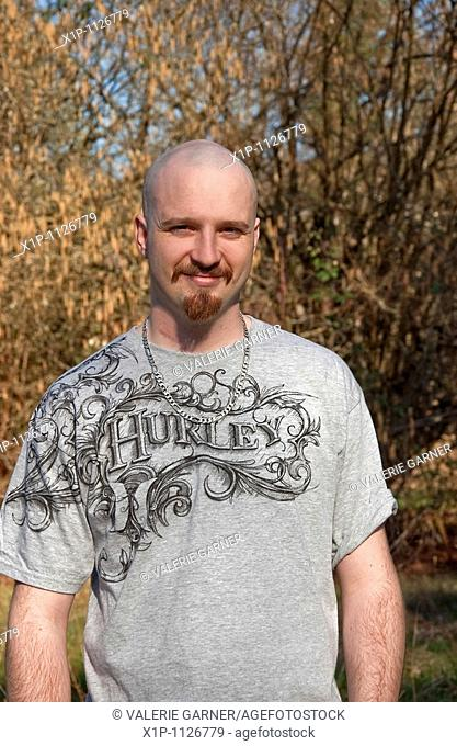 This vertical portrait of a mid-twenties Caucasian man, smiling outdoors in early spring He has light skin and a warm smile, a goatee with his head shaved bald