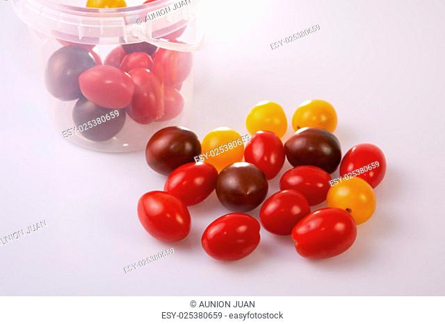 Bucket and colorful cherry tomatoes. Isolated over white background