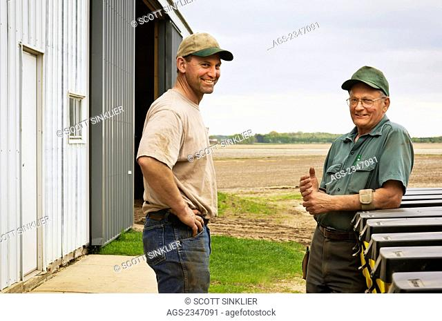 Agriculture - Father and son farmers pose while discussing Spring planting operations on their farm / Central Iowa, USA