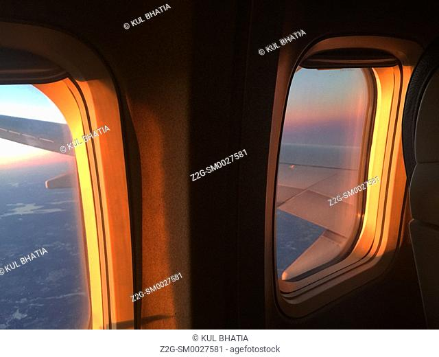 Warm glow from the setting sun filters inside a small plane in flight through two windows, Ontario, Canada