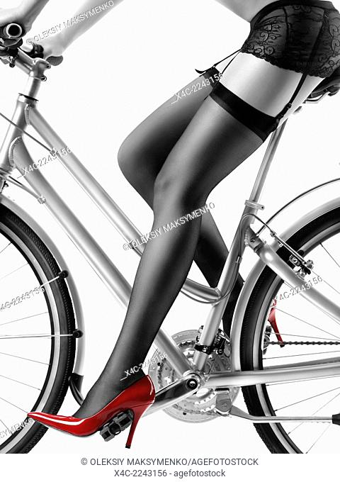 Legs of a woman in black stockings and sexy red high heel shoes riding a bicycle isolated on white background. Black and white with red color