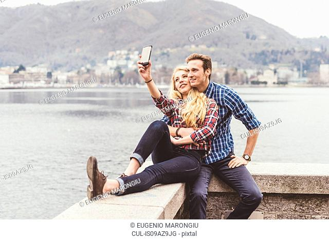 Young couple sitting on harbour wall taking smartphone selfie, Lake Como, Italy