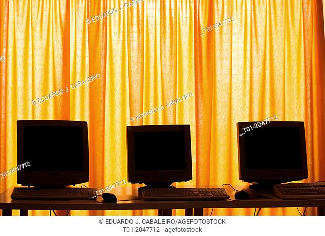 three computer screens on yellow curtains
