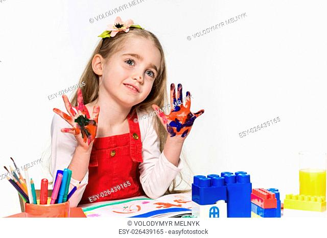 The beautiful little girl with hands in the paint on the white background