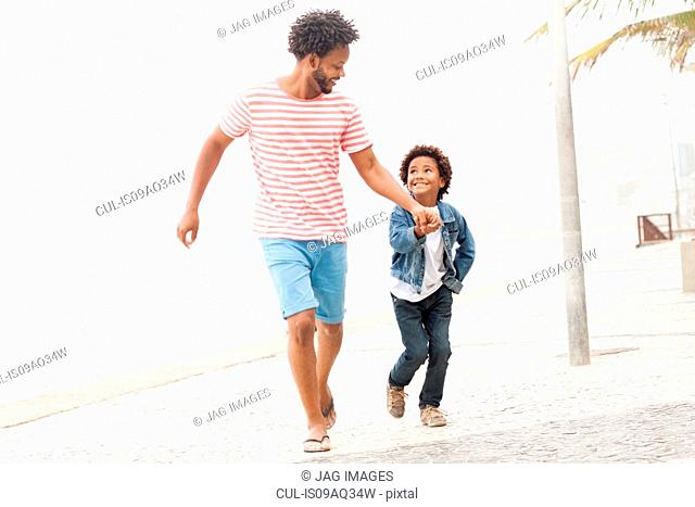 Father and son running hand in hand at Ipanema beach, Rio De Janeiro, Brazil