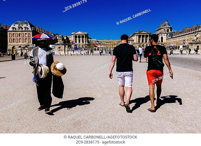African immigrant selling things to tourists in front of Palace of Versaille main entrance. Versailles, Île-de-France, France