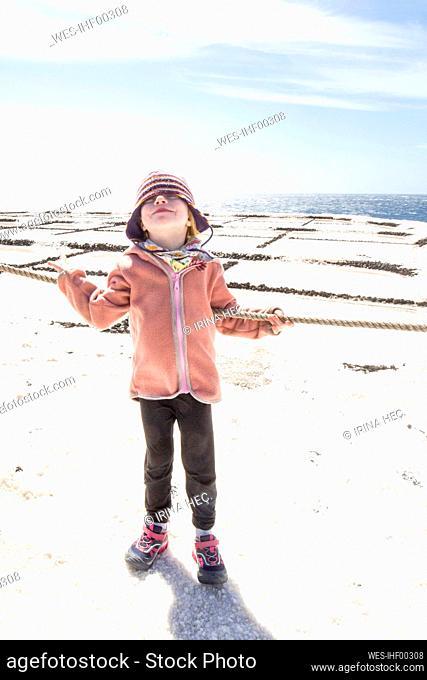 Little girl standing in front of salt pans, Fuencaliente, La Palma, Spain