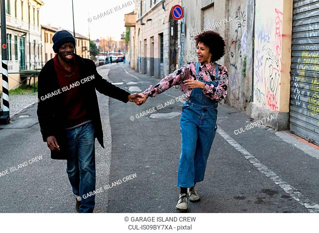 Cool young couple holding hands along city alleyway