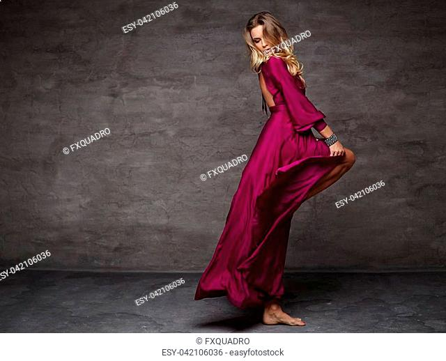 Dancing blond girl in long red dress on grey background