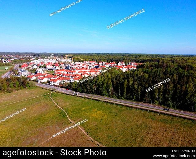 New buildings of estate surrounded by fields and forests, view from a drone, Gdynia, Poland