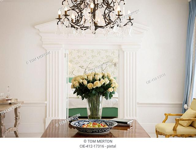 Chandelier above rose bouquet on table in luxury foyer