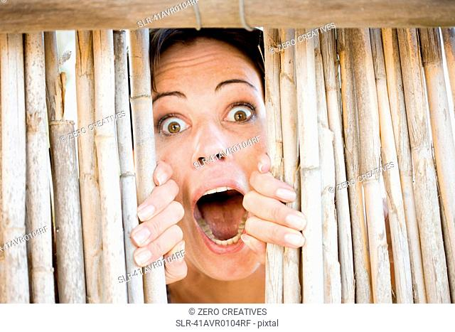 Close up of woman gasping behind fence