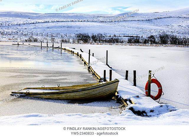 Small rowing boat used for fishing, sunk by the weight of snow, loch on Eaglesham Moor, near Glasgow, Scotland, UK. Image taken about 1 mile south of Eaglesham