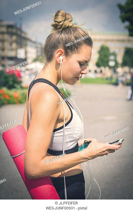Young woman with yoga mat, cell phone and earphones in the city