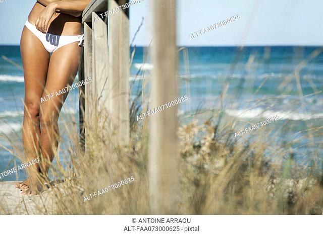 Woman leaning against railing at the beach, cropped