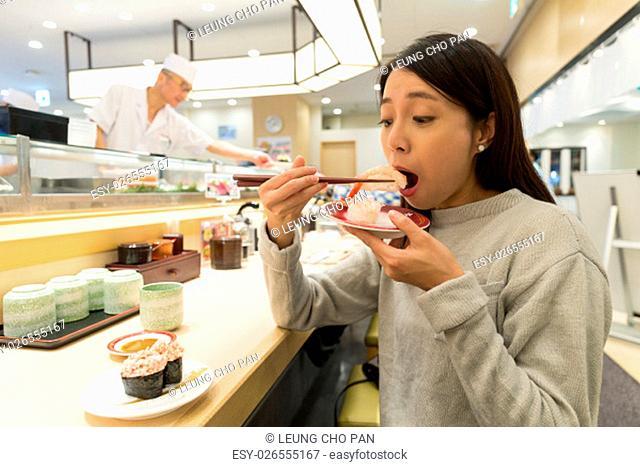 Woman eating sushi in japanese restaurant