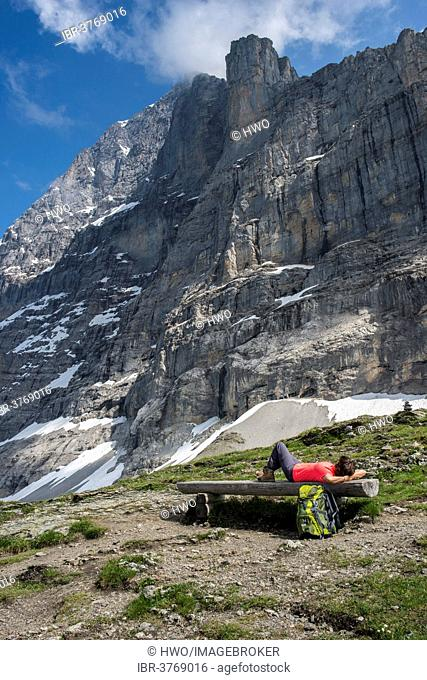 A hiker lying on a bench on the Eiger Trail, behind the Eiger North Face, Swiss Alps Jungfrau-Aletsch UNESCO World Heritage, Grindelwald, Canton of Bern