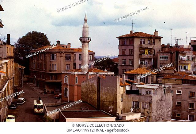 Scene of a single white minaret rising above the surrounding apartment buildings in a neighborhood of Istanbul, Turkey, November, 1973